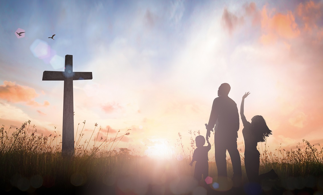 Family worship concept: Silhouette father mother and son looking for the cross on autumn sunrise background.